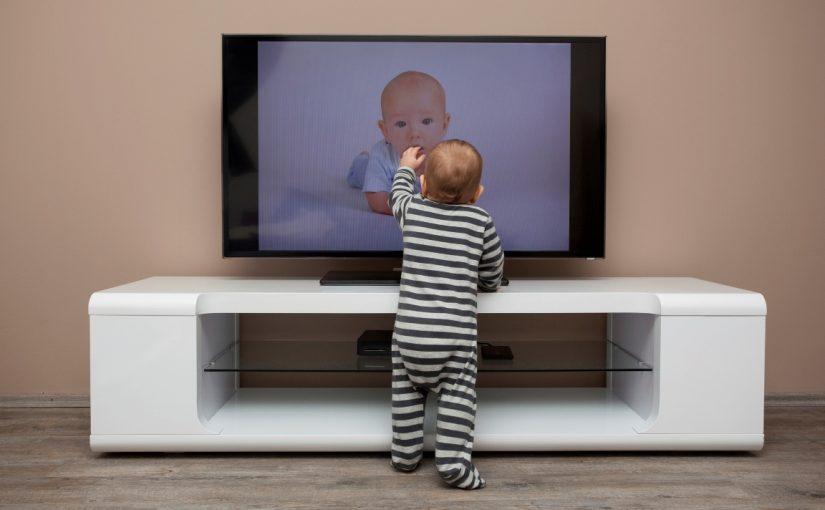 ребенок перед телевизором тыкает пальцем в экран