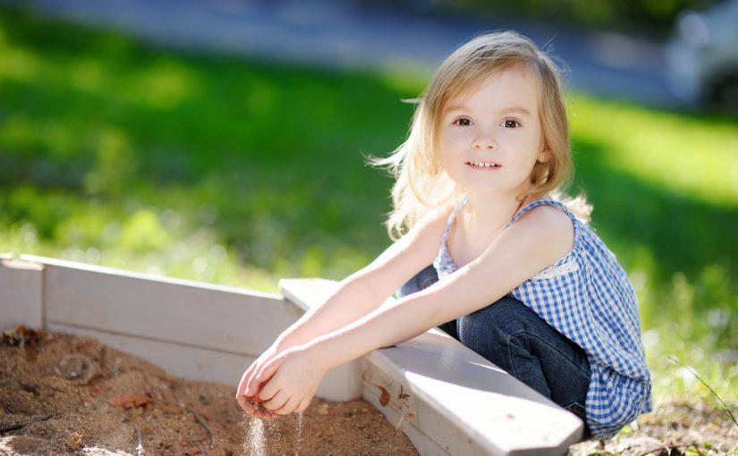 симпатичная девочка с ведрышком и совочком в песочнице сидит играет улыбается, солнышко трава зеленая