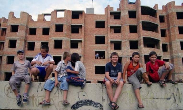 дети лазают на заброшенной стройке, ходят по бетонным плитам