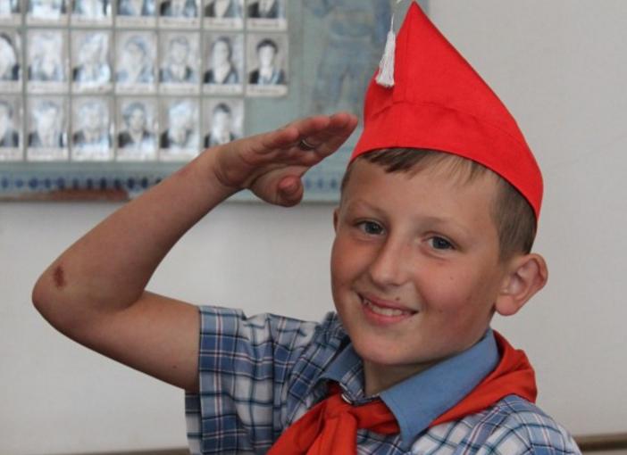 мальчик очень рад тому что его приняли в пионеры, красный галстук платок и пилотка