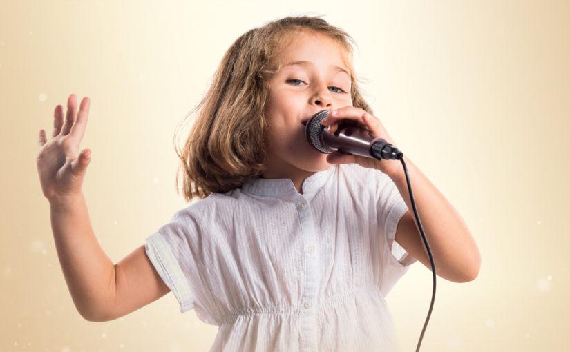 Девочка поет в микрофон и танцует